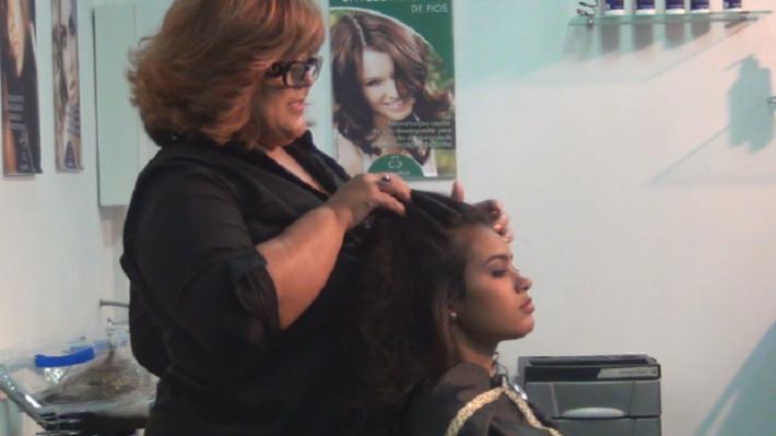 Bete Omori executando um de seus penteados em curso da Mart'bel com apoio da Grandha.