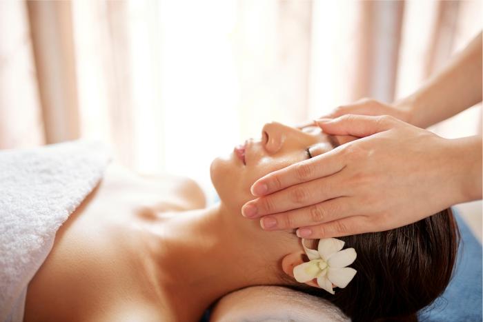 Mulher recebendo massagem terapêutica com óleo de semente de uva.