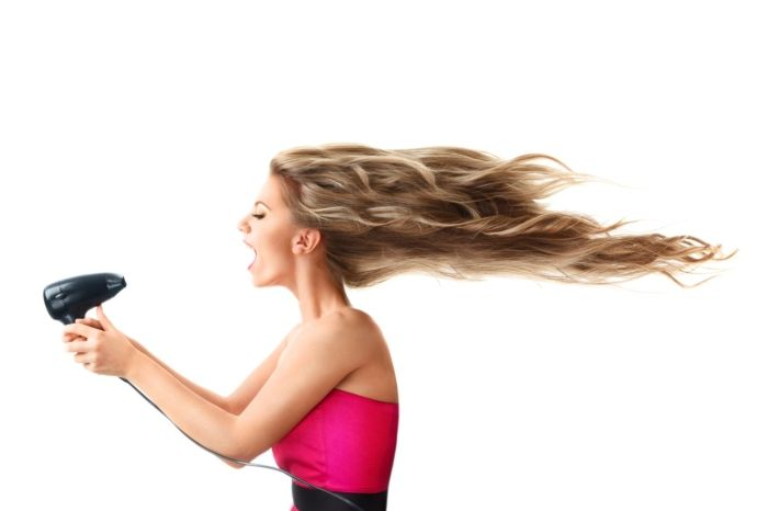 Mulher com secador de cabelo.