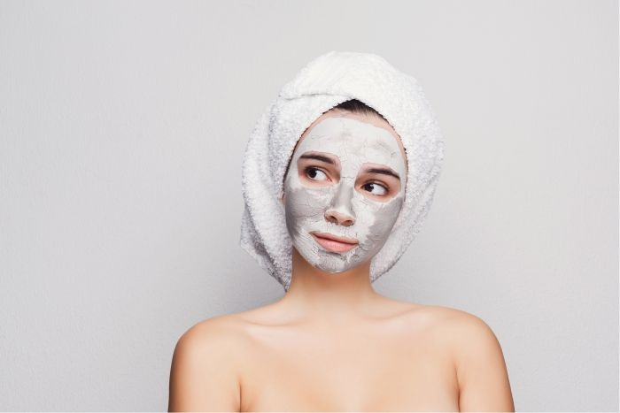 Mulher com máscara de argila branca.