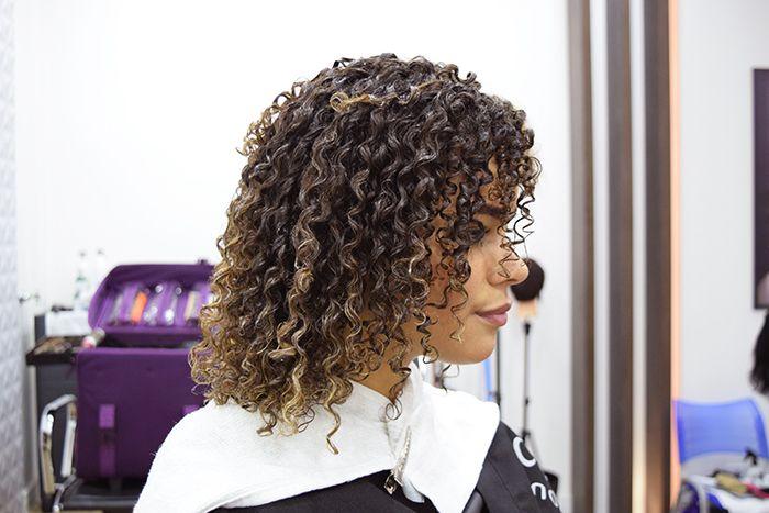 Mulher com corte de cabelo cacheado curto com luzes.