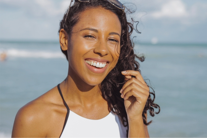 Mulher negra cuida de cabelo em piscina e praia.