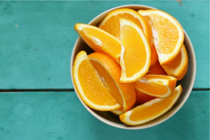 Laranjas cortadas sobre a mesa. Óleo da fruta pode ser benéfico em aromaterapia para gestantes.