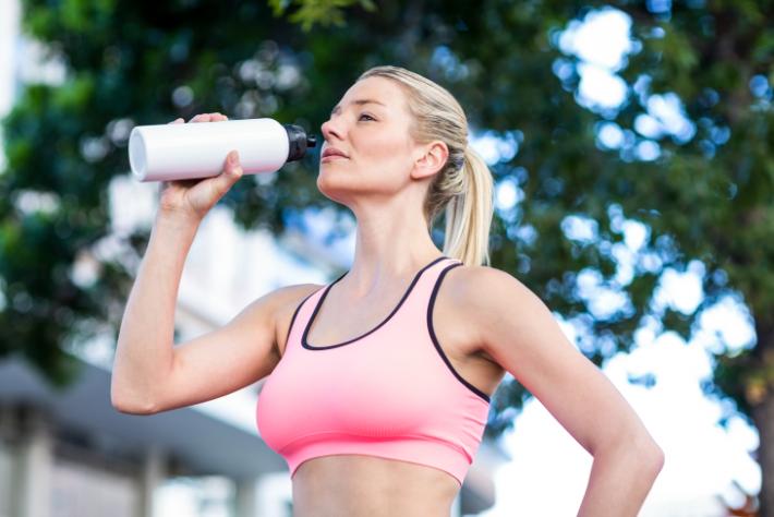 Mulher praticando esportes bebe água.