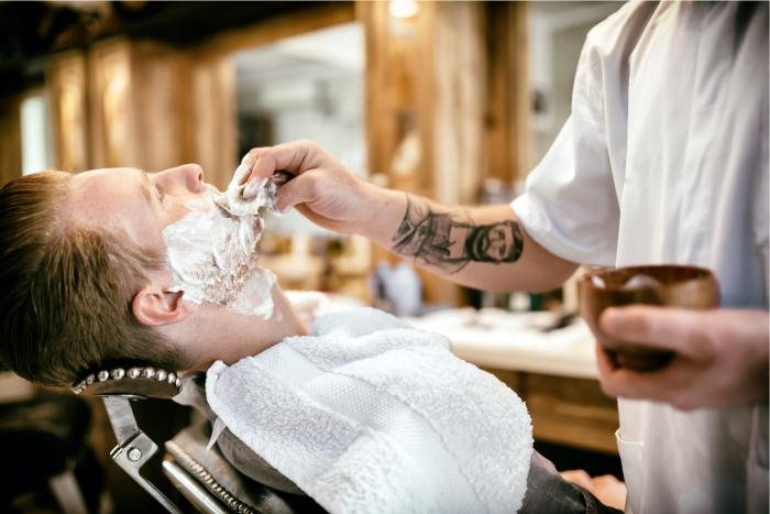 Barbeiro prepara cliente para tratamento de foliculite e remoção da barba.