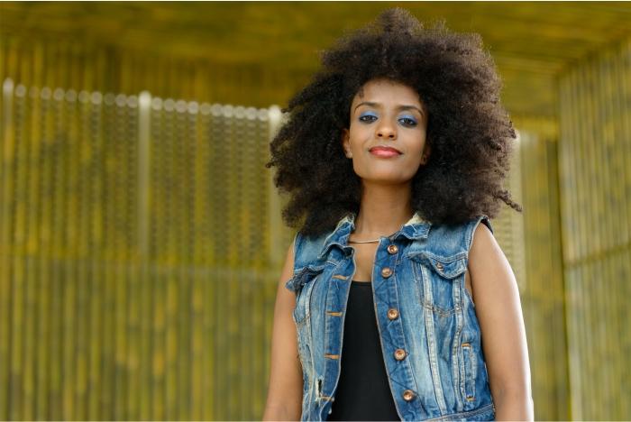 Mulher com couro cabeludo afro ou crespo, cuidados e fisiologia da pela negra.