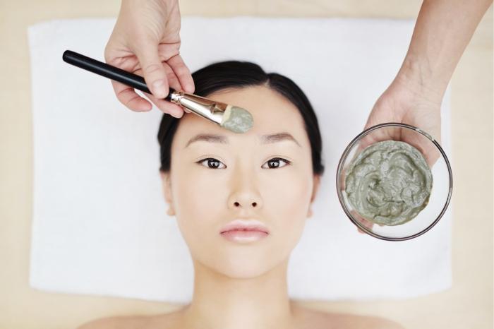 Mulher aplicando argila verde no rosto.