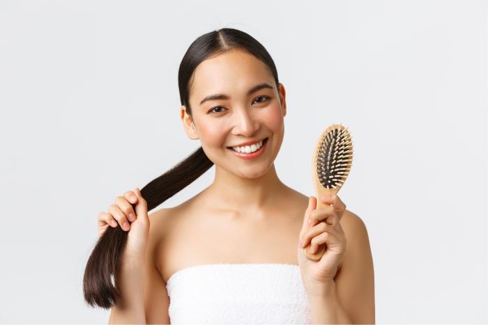 Mulher asiática escova cabelo com produto com 18-MEA.